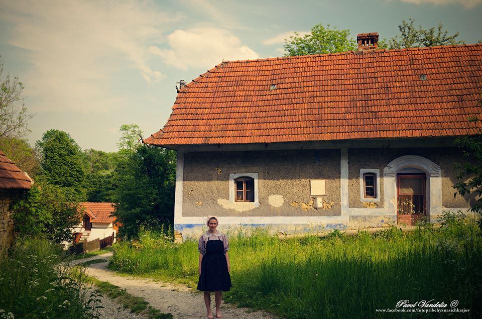 žena v kroji, starý dom