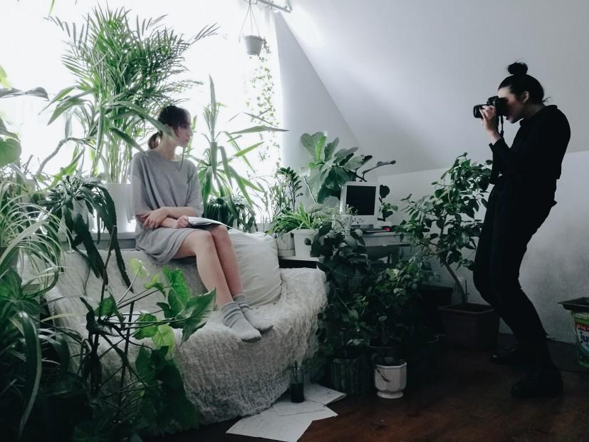 Evelyn Benčičová fotiaca ženu na gauči, rastliny