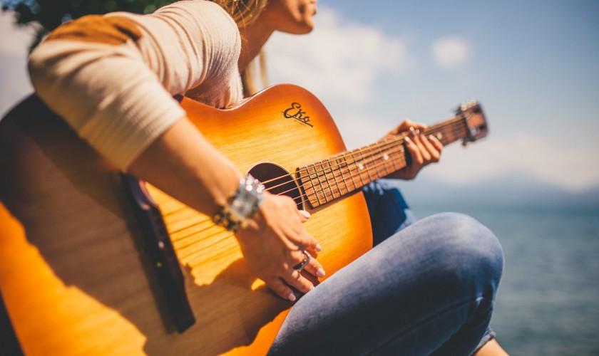 žena hrajúca na gitare