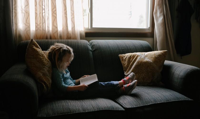 dieťa čítajúce knihu na gauči